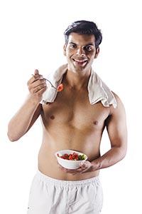 Fitness Bodybuilder Man Eating Fresh Salad