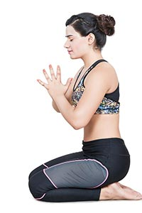 Woman Practising Yoga kneeling Joined Hands