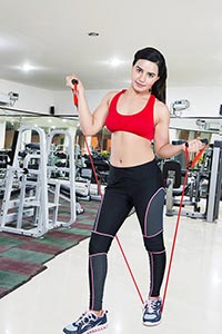 Woman Exercising Pull Elastic Rope Gym
