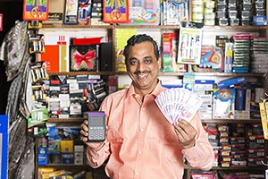 Shopkeeper Man Showing Money Credit Card Reader