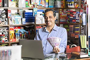Stationery Shop Shopkeeper Man Laotop Showing Mone
