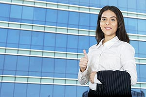 business woman thumbsup outside office building