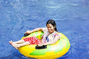 Young Woman relaxing inflatable ring resort pool