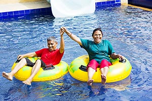 Seniors Couple Relaxing inflatable ring resort poo