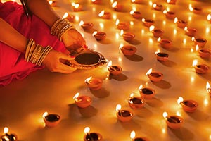 Traditional Indian woman lighting Diya Divali Fest