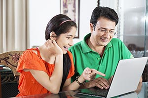 Daughter pointing something Father laptop smiling