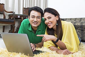 Indian Couple Lying Floor Laptop Pointing Smiling