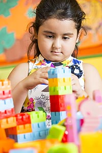 Little girl Preschool playing toy blocks Classroom