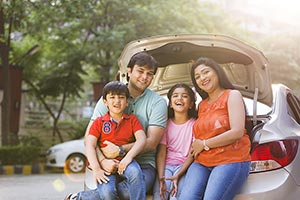 Happy Indian Family sitting at the back of a car E
