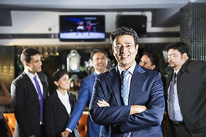 Indian Businessman Standing In Bar with colleagues