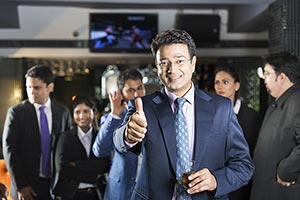 Businessman Standing In Bar Showing Thumbs up with