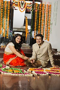 Couple Decorating Diwali Rangoli Diya At Home